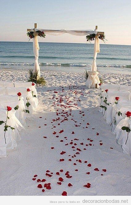 Decoración boda en la playa con tul y pétalos rojos