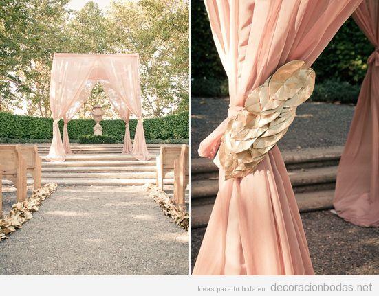 Decoración de boda en jardín con tela rosa y hojas secas