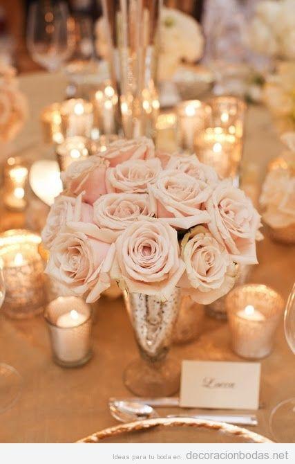 Decoración de mesa de bodas con jarrones de plata vieja, rosas y velas