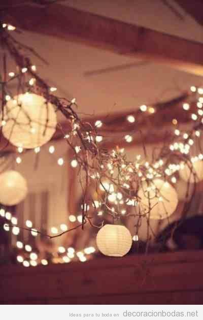 Decoración salón boda con ramas, luces y lámparas de papel