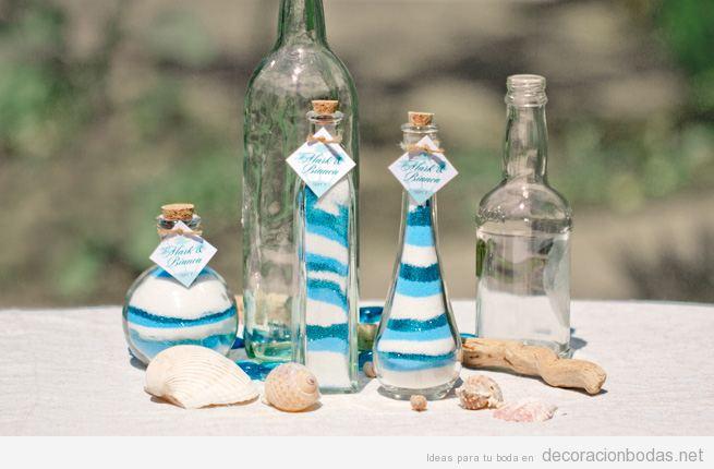 Decorar mesa de boda en playa con botellas de arena, caracolas y troncos