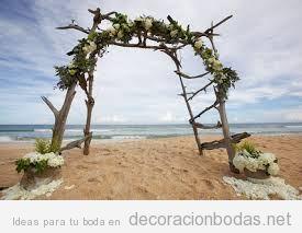 Altar hecho con troncos y flores, boda en la playa