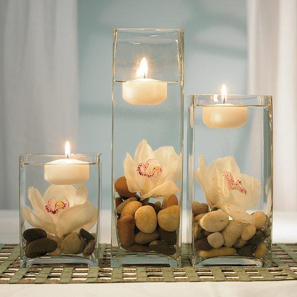 Jarrones de cristal, piedras, flores blancas y velas para decorar mesas de boda