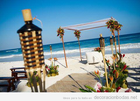 Decoración con antorchas y flores tropicales para una boda en la playa