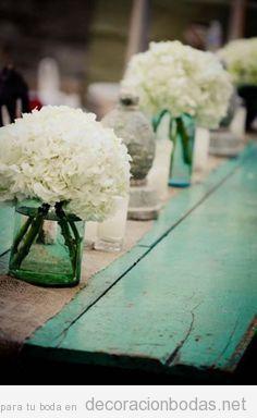 Mesa de madera turquesa y flores blancas