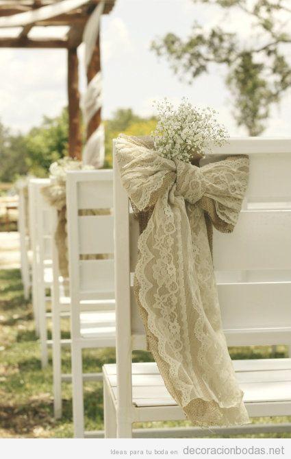 Sillas de madera blanca y lazos de blonda beige para boda en el jardín