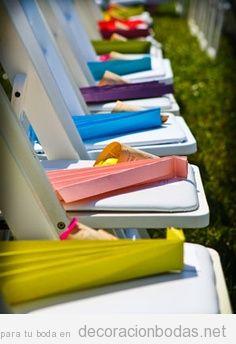 Abanicos de papel de colores en sillas de jardín, un detalle para los invitados