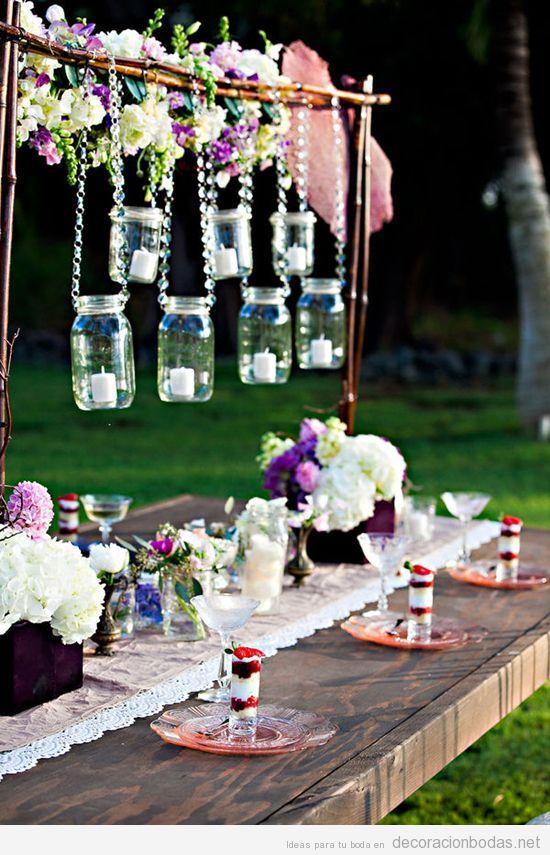 Mesa de boda en jardín decorada con botes de cristal, vintage