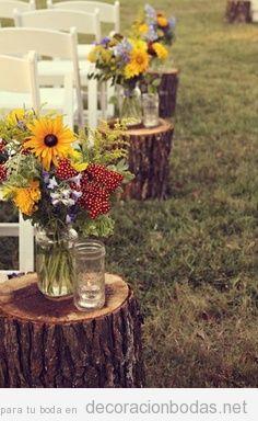 Pasillo hacia el altar con troncos de árboles y flors