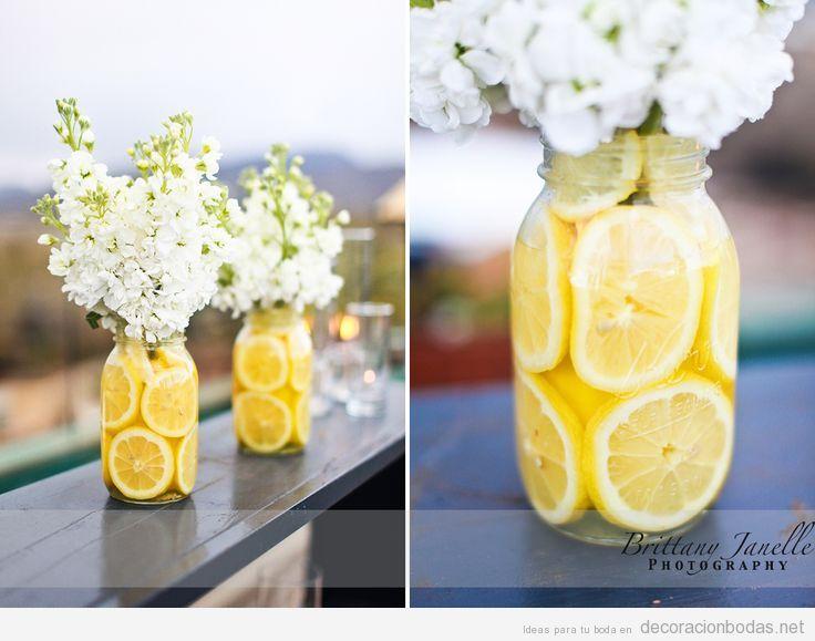 Jarrón con rodajas de limón y flores blancas para decorar una mesa o barra en una boda