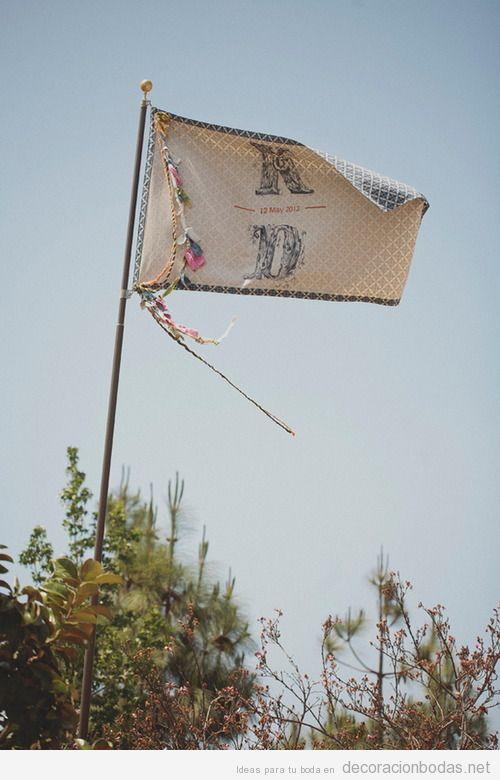 Una bandera con las iniciales de los novios y la fecha para dar la bienvenida