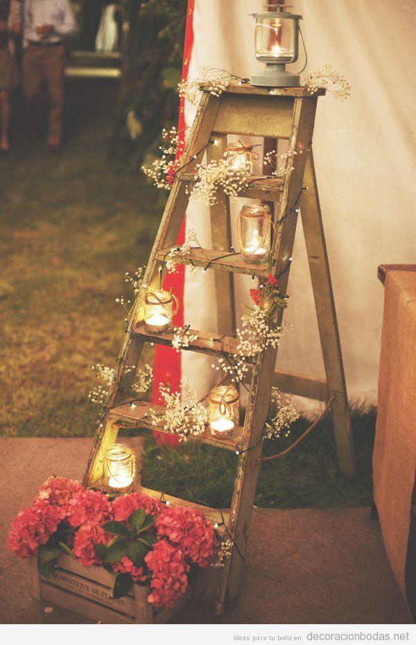 Una escalera de madera llena de flores y velas, precioso detalle para decorar un rincón