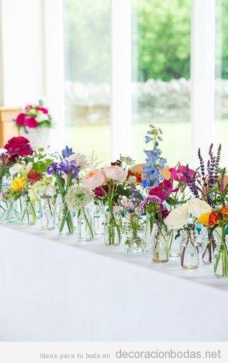 Botes de cristal con distintas flores de colores muy vivos para decorar mesa alargada