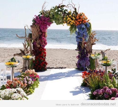 Un altar hecho de troncos y flores de muchos colores para boda en la playa