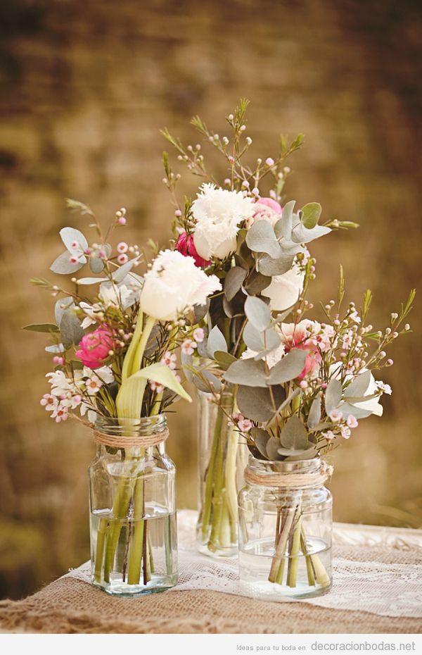 Centro de mesa con botecitos de cristal y flores silvestres