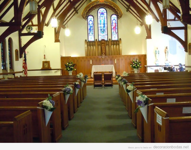 Conos de papel con flores para decorar los bancos de una iglesia en una boda