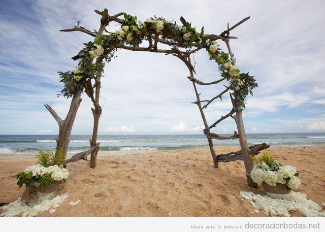 Altar hecho con ramas y flores blancas para casarse sobre la arena de la playa